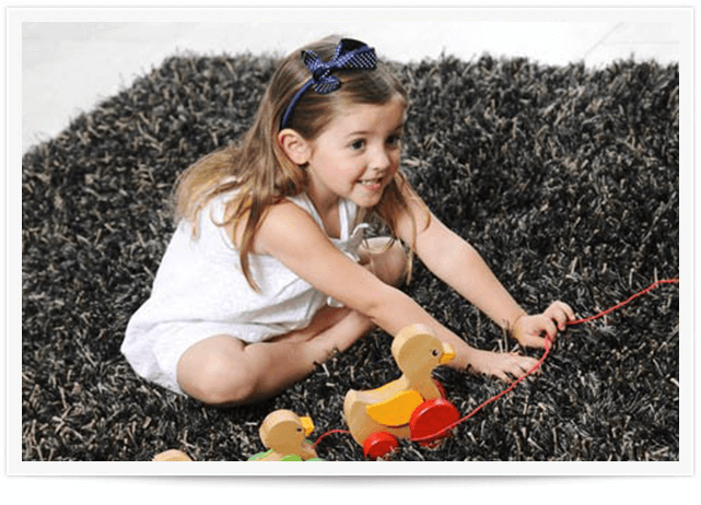 girl playing with toys on gray area rug in atlanta home