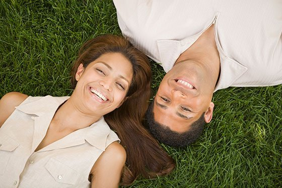 couple laying in green grass