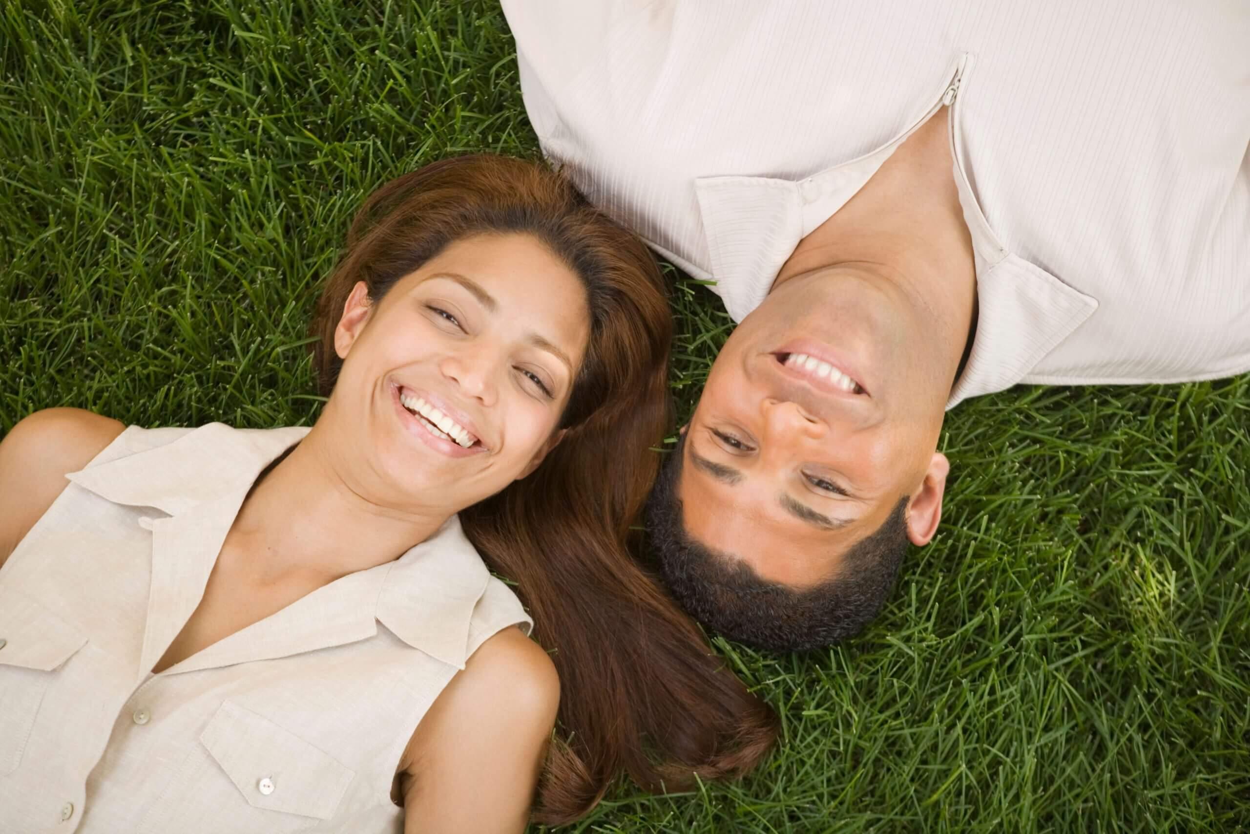 couple laying in green grass in atlanta
